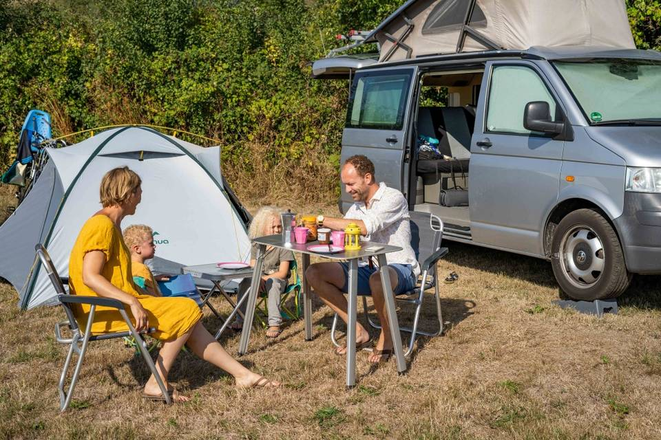 Family eating breakfast in front of their campervan