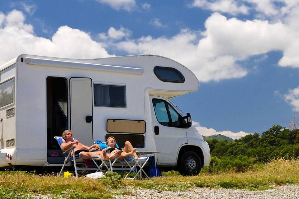 Couple relaxing in front of their rental motorhome