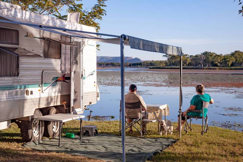 Two people sitting under the awning of their caravan