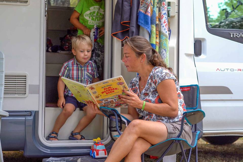 Mother and child reading a book in a motorhome