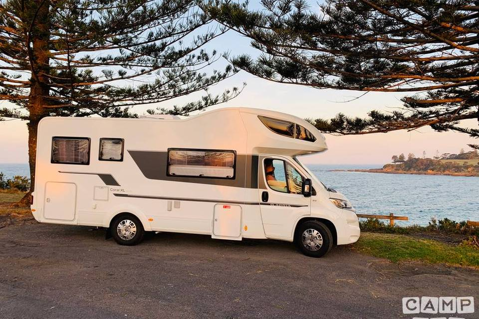 People in front of an alcove motorhome near a lake