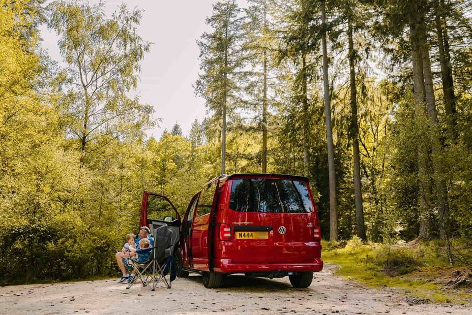 Red volkswagen campervan in the forest